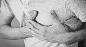 Black and White Photo of Man Clasping Chest